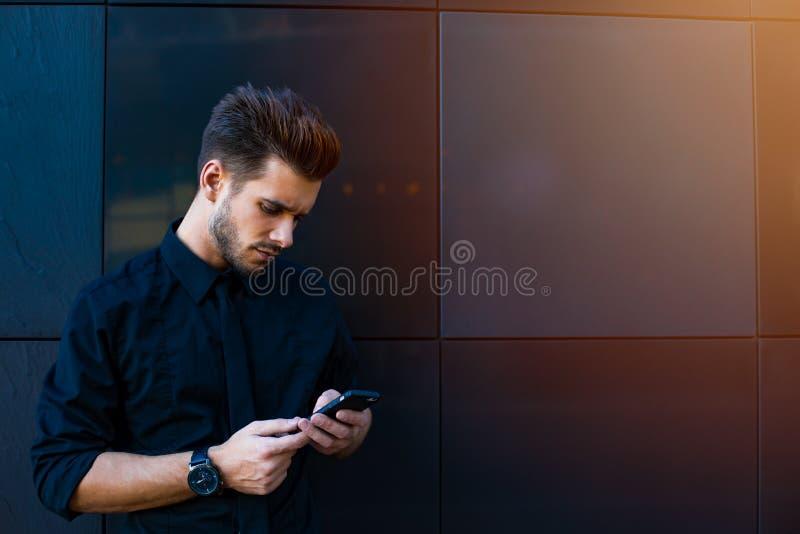 Directeur qualifié envoyant des sms par l'intermédiaire du téléphone portable image libre de droits