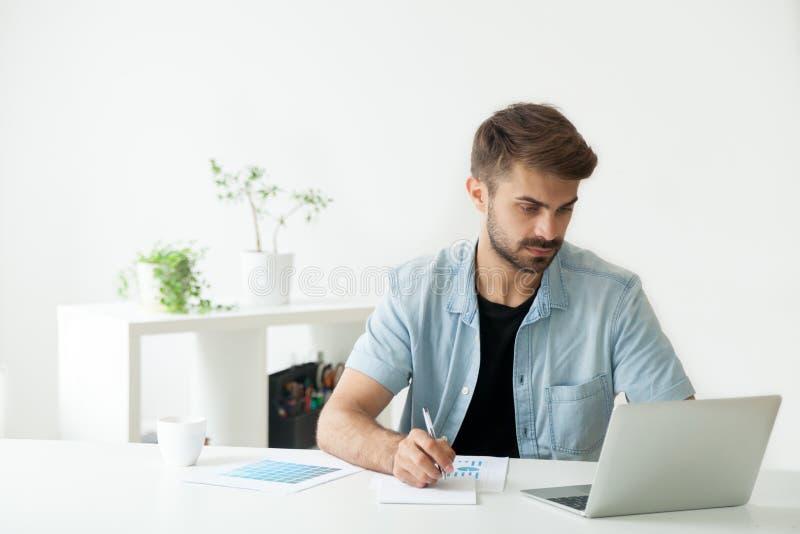 Directeur sérieux travaillant à l'ordinateur portable analysant des rapports financiers photographie stock libre de droits