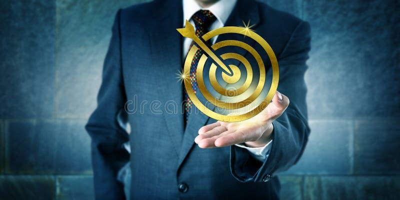 Directeur Showing une icône d'or de cible dans la paume ouverte photographie stock libre de droits