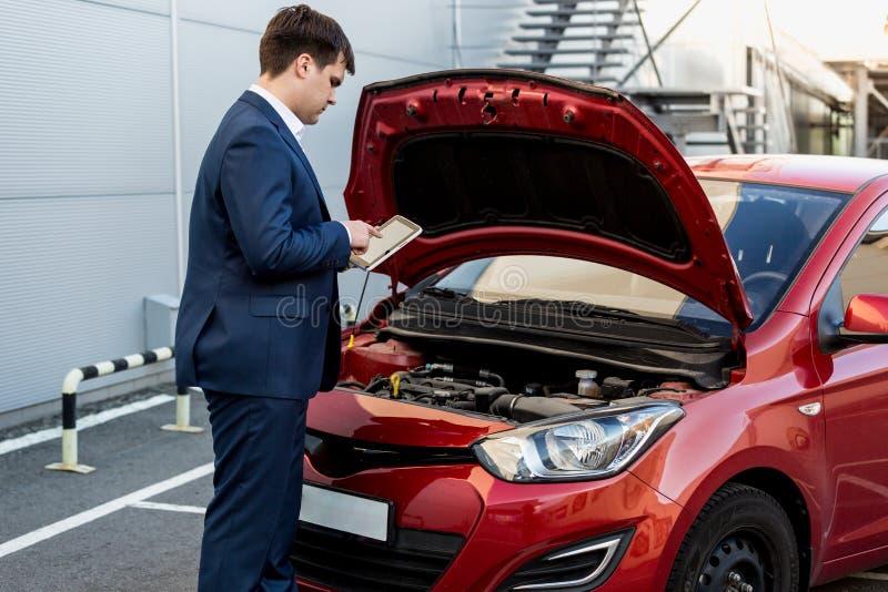Directeur vérifiant la condition de voiture sur le comprimé photographie stock libre de droits