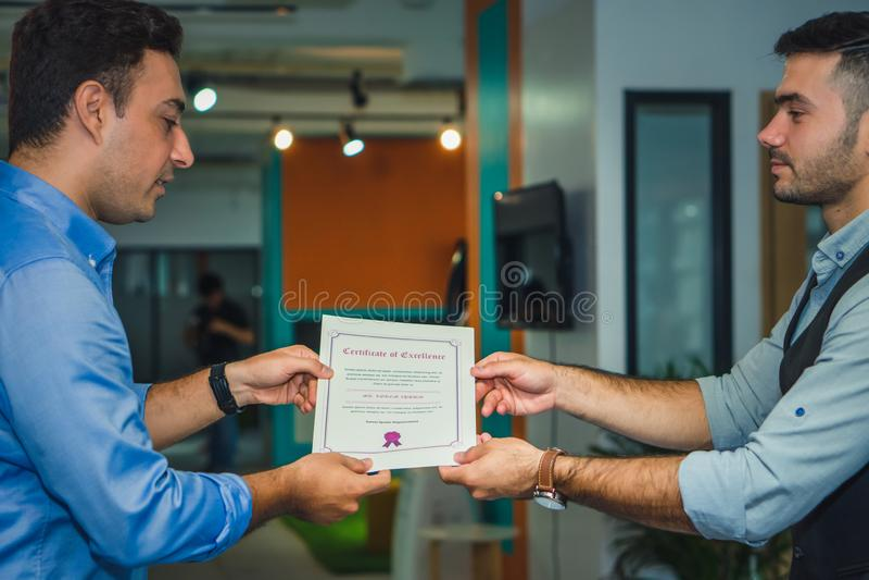 Directeurbeheer die gelukwens hebben aan uitvoerend personeel dat toekenning met certificaat krijgt stock afbeelding