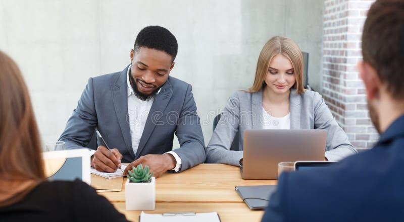 Directeurs d'heure interviewant des demandeurs de travail, faisant des notes photo stock