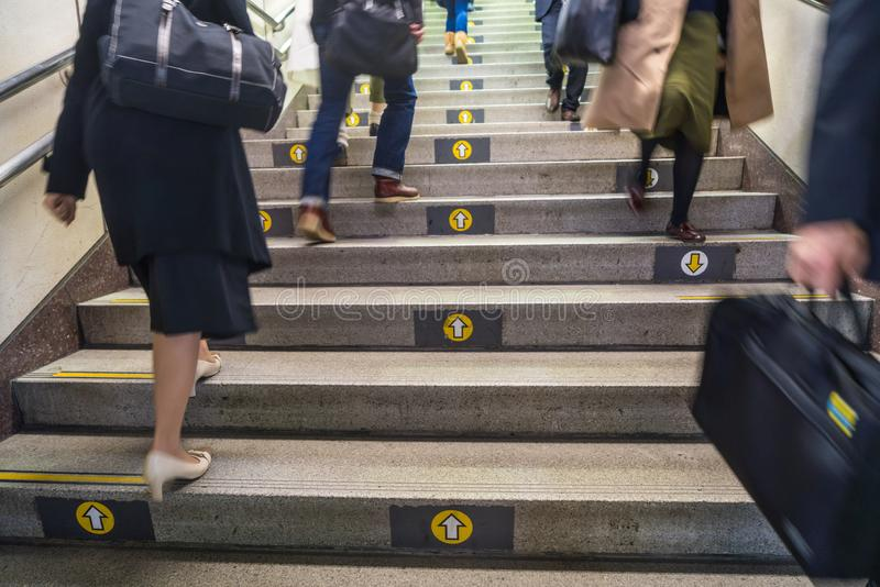 Direction arrows on steps on Tokyo subway with commuters, Tokyo royalty free stock image