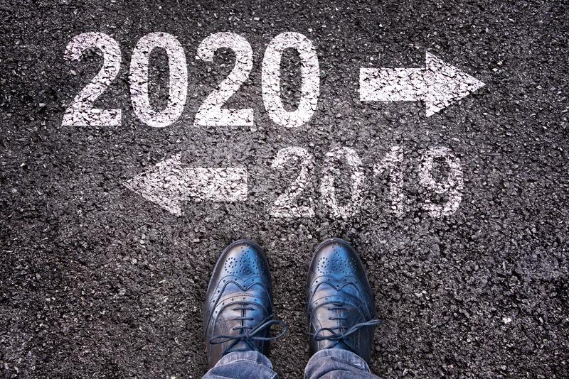 2020 and 2019 with direction arrows written on asphalt road background with legs stock image