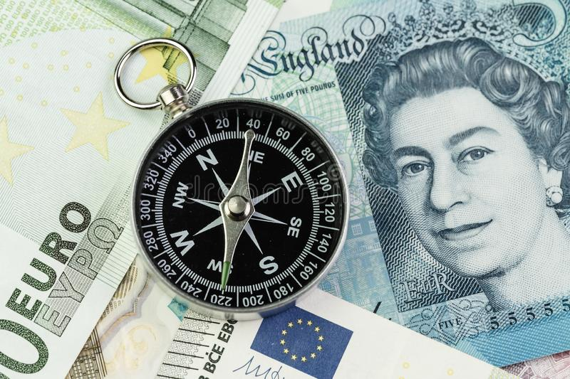 Direction of Europe and UK after Brexit negotiation concept, compass on Euro and UK Pound banknotes.  stock images