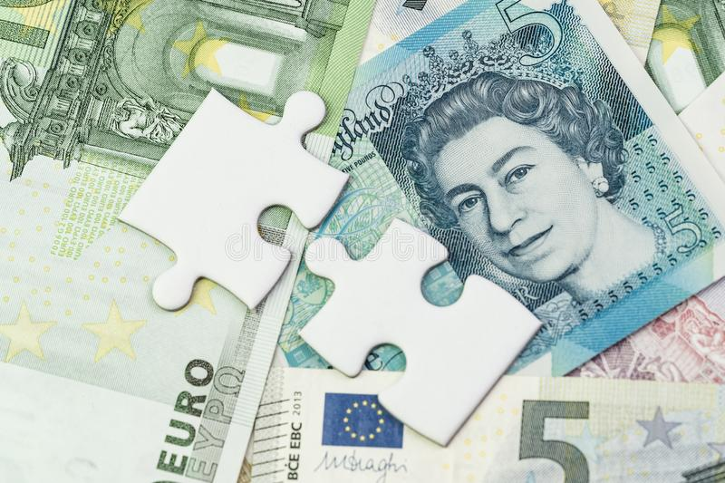 Direction of Europe and UK after Brexit negotiation concept, jigsaw puzzle metaphor on Euro and UK Pound banknotes.  stock images