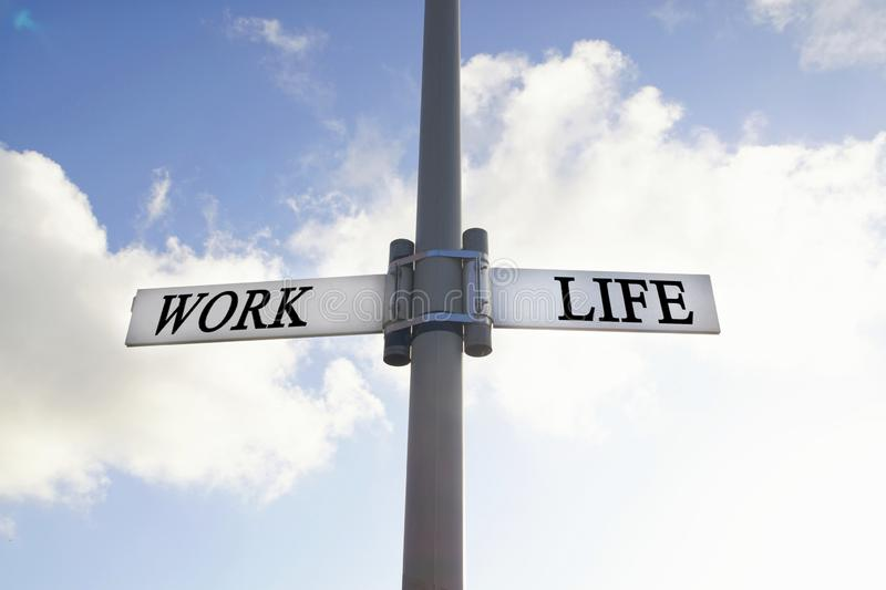 Direction road sign with work and life words. Life balance choices signpost, with blue cloudy sky background royalty free stock images