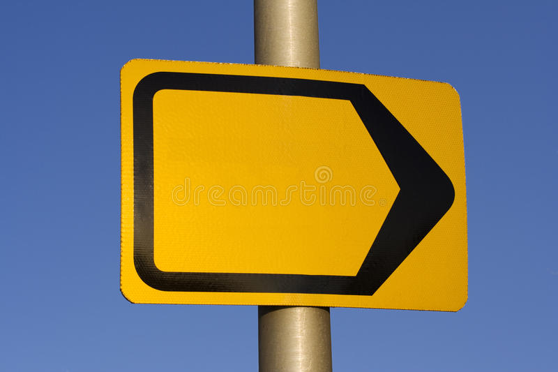 Direction sign. Empty yellow direction sign with black lining on metal pole. Against blue sky. Add your own text or logo stock image