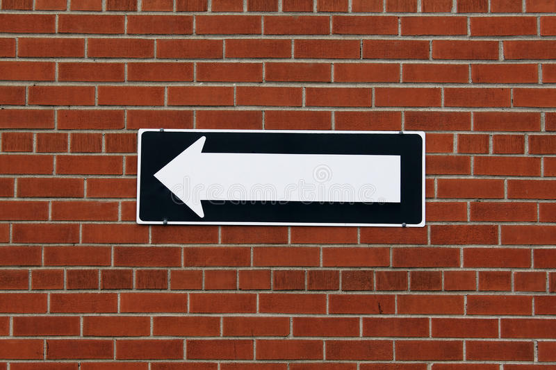 Direction sign on a brick wall