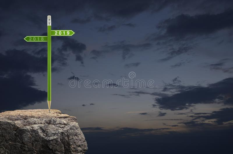 2019 and 2018 direction sign plate with green pencil on rock mountain over sunset sky, Business strategy planning concept, Happy royalty free stock photo