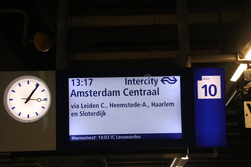 Direction sign on platform with clock and platform number on Den Haag Centraal Station stock photography