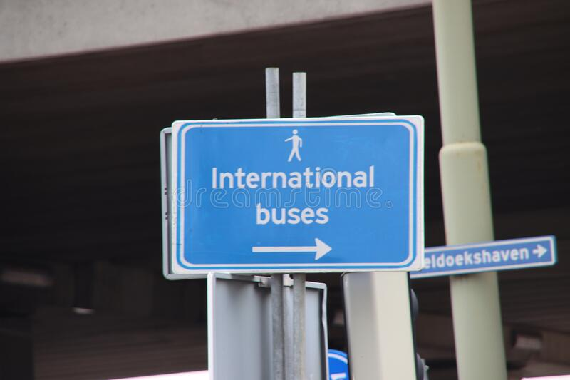 Direction sign to the bus stop for the international buses at Den Haag Central Station stock photography