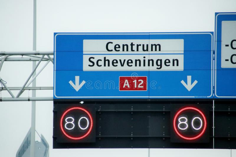 Direction sign with white for local destinations to Center and Scheveningen and mandatory speed limit below it on highway A12 in t stock photography