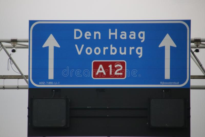 Direction sign with white for local destinations to Den Hag and Voorburg and mandatory speed limit when lit below it on highway A1 stock image
