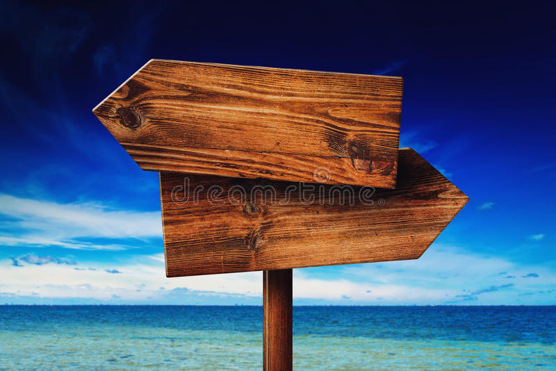 Direction signpost on seaside beach. Rustic wooden blank sign in summer vacation resort stock images