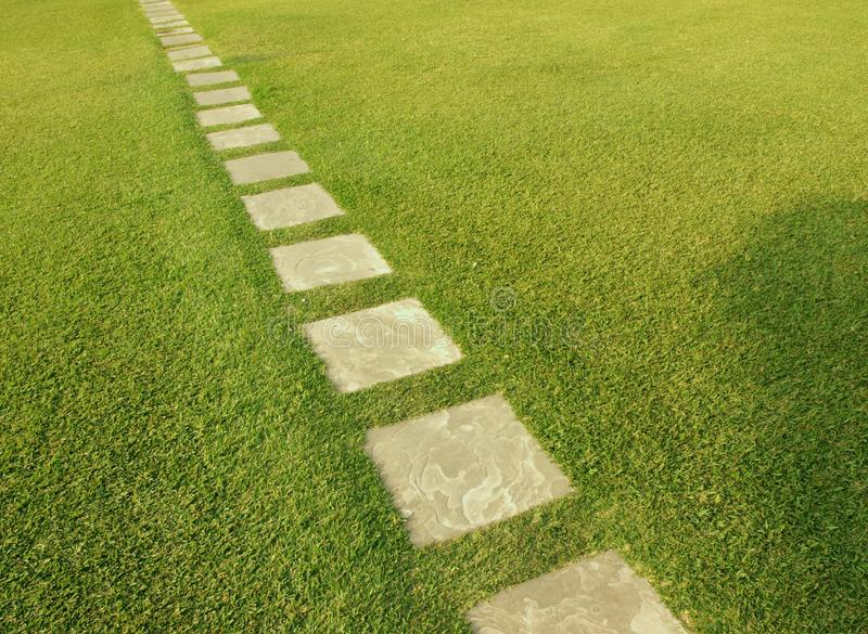 Direction of tile path through fresh cut grass stock photography