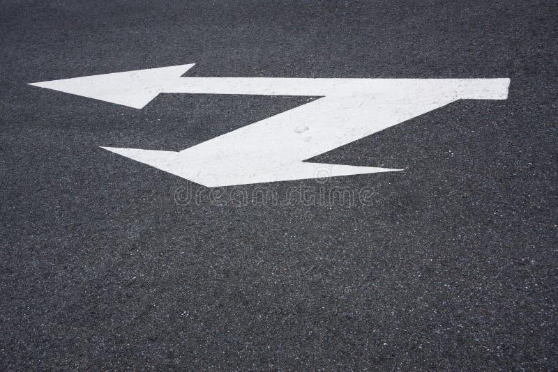 Directional arrow sign on asphalt