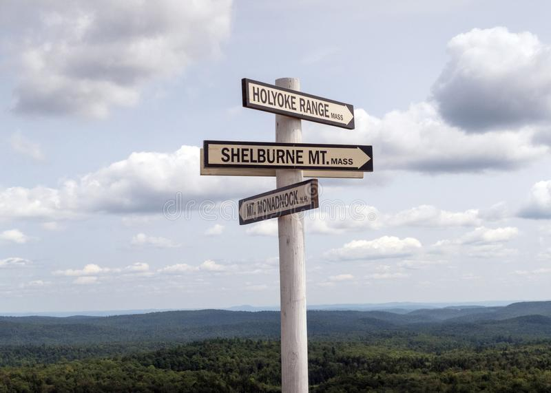 Directional sign post atop Hogback Mountain, Vermont. Wooden white directional sign post atop Hogback Mountain, Wilmington, Vermont, tourist stop with 100 mile stock image