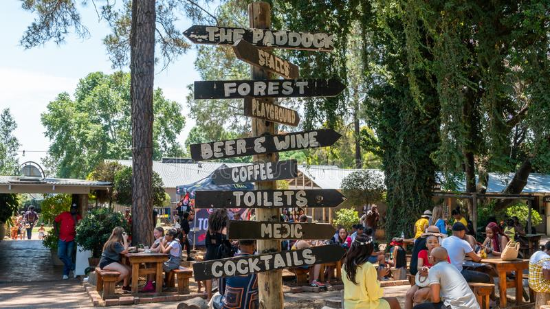 Directional signage in Fourways Farmers Market with people eating and socializing, Johannesburg, South Africa. Johannesburg, South Africa - October 2019 stock photography