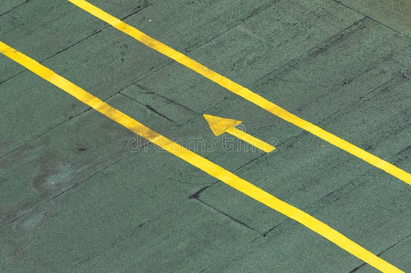 Directional traffic yellow arrow on a green tarmac texture floor. stock images