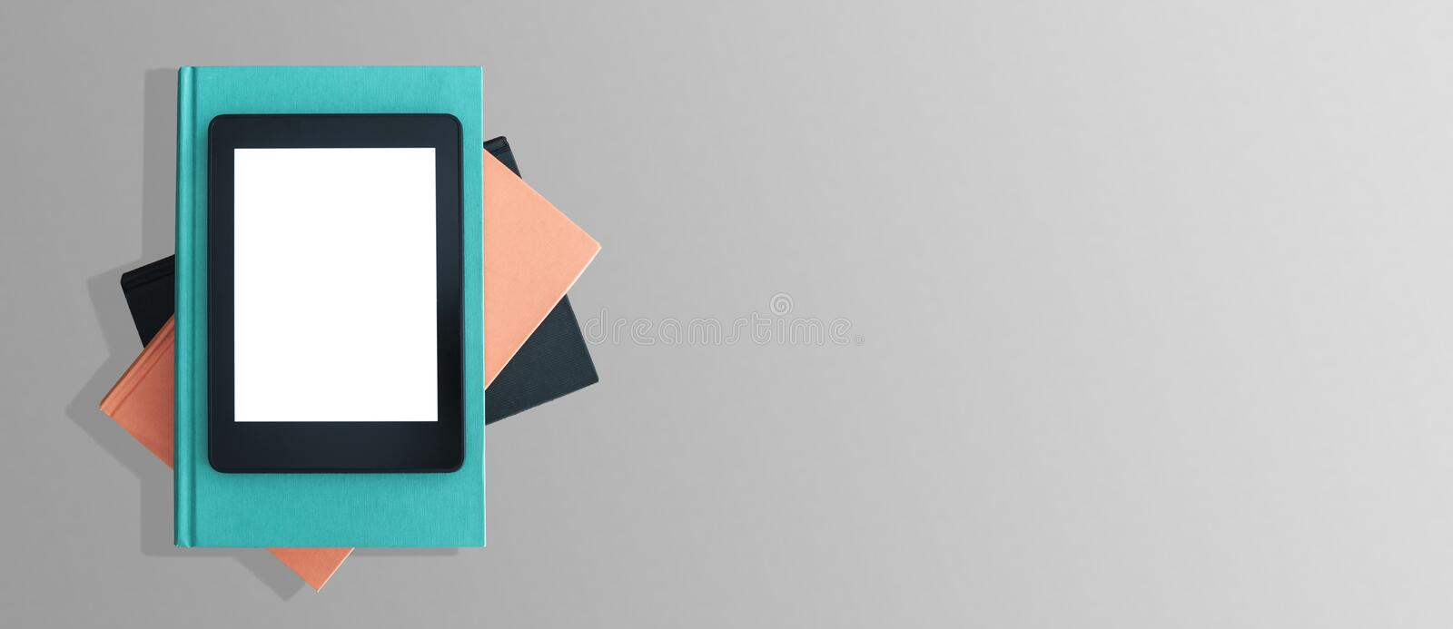 Top view of e-book reader on stack of books on gray desktop royalty free stock photo