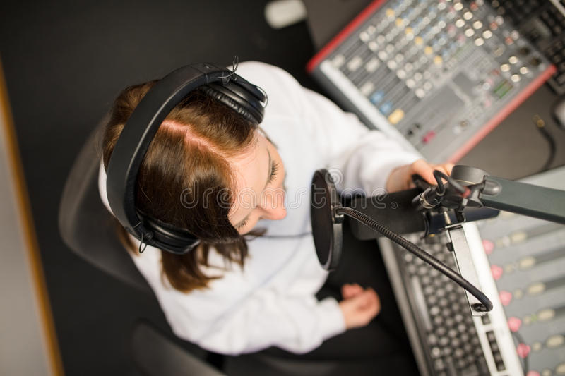 Directly Above Shot Of Radio Jockey Using Microphone And Headpho. Directly above shot of female jockey using microphone and headphones in radio studio stock photography