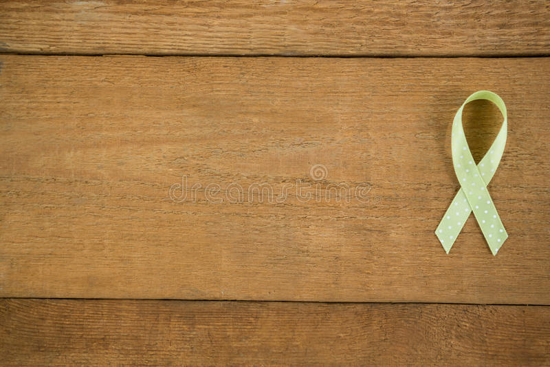 Directly above view of spotted green Lymphoma Awareness ribbon. On wooden table royalty free stock image