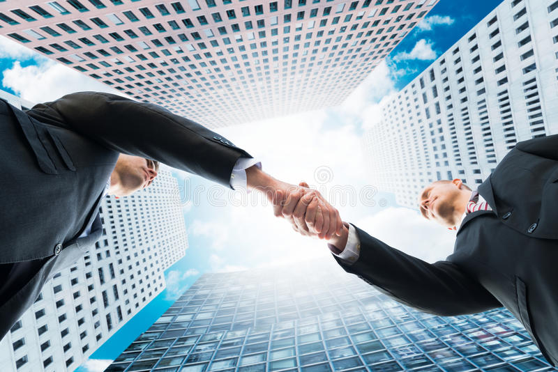 Directly Below Shot Of Businessmen Shaking Hands. Against office buildings stock photography