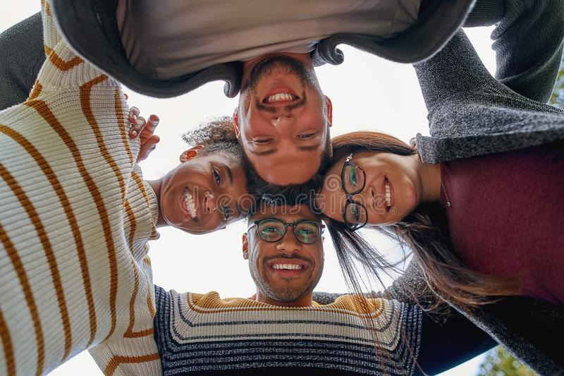 Low angle view of happy friendly diverse multi-ethnic friends forming a circle and looking at camera smiling - teamwork royalty free stock photos