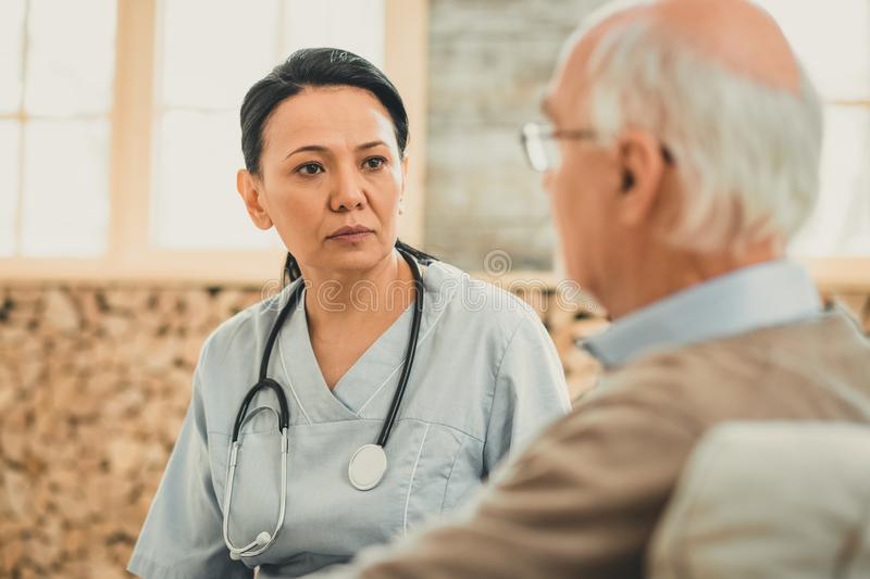 Executive nurse seriously looking on her old patient. Directly looking. Executive nurse seriously looking on her old patient during severe conversation about his stock image