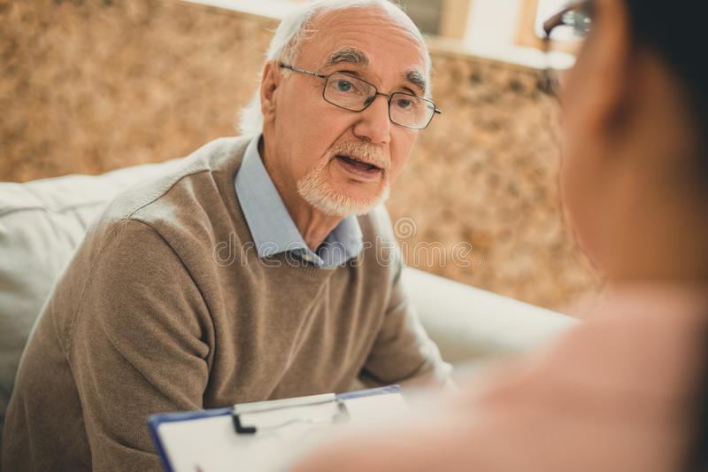 Exhausted senior with white beard asking his volunteer. Directly looking. Exhausted senior with white beard asking his volunteer about his conditions in royalty free stock photos
