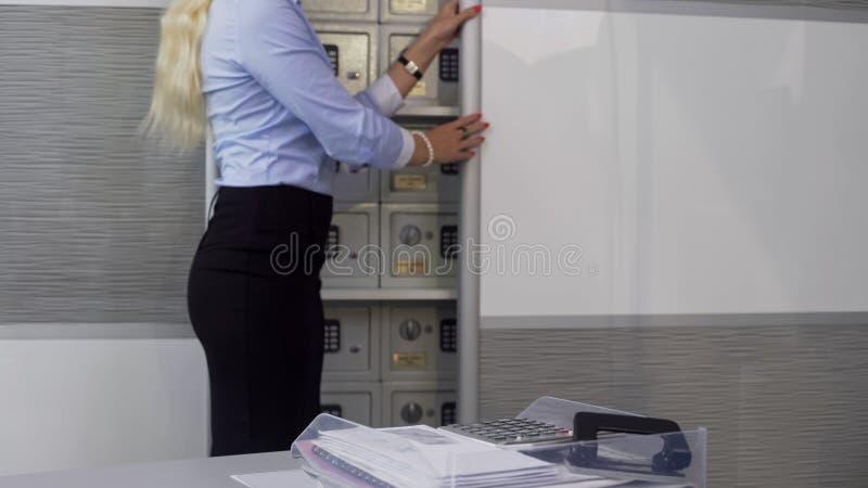 Director de banco que muestra a clientes las cajas de depósito, almacenamiento seguro de cosas valiosas fotografía de archivo libre de regalías