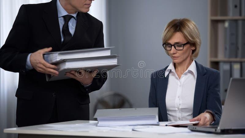 Director del bufete de abogados que da casos con los ficheros de clientes importantes a los empleados imagen de archivo libre de regalías