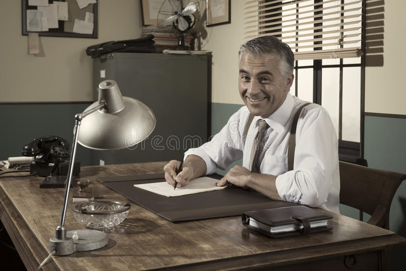 Director at desk signing a document. Vintage style office stock image