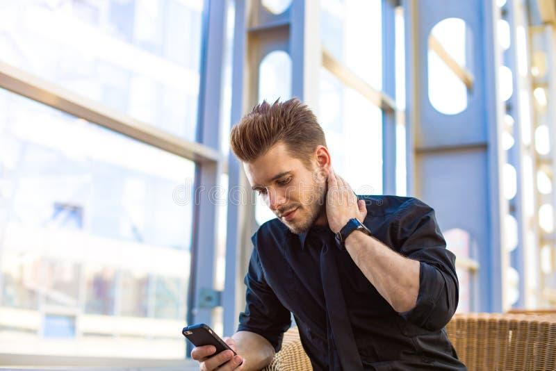 Director ejecutivo acertado del hombre usando mensajero en el teléfono móvil, sentándose en interior de la oficina imagen de archivo libre de regalías