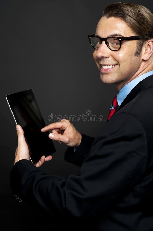 Director empresarial joven que trabaja en su PC de la tablilla fotos de archivo libres de regalías