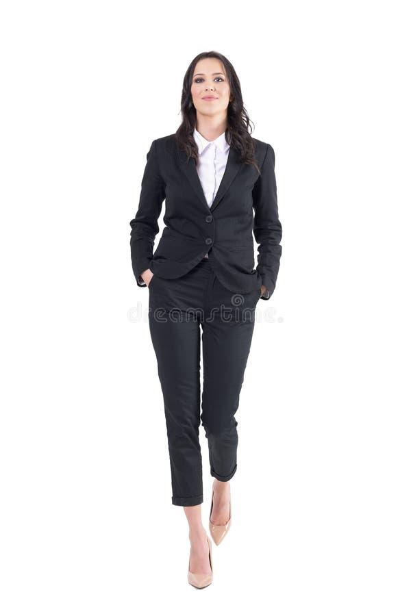 Director empresarial o abogado de sexo femenino acertado que camina con las manos en bolsillos fotos de archivo