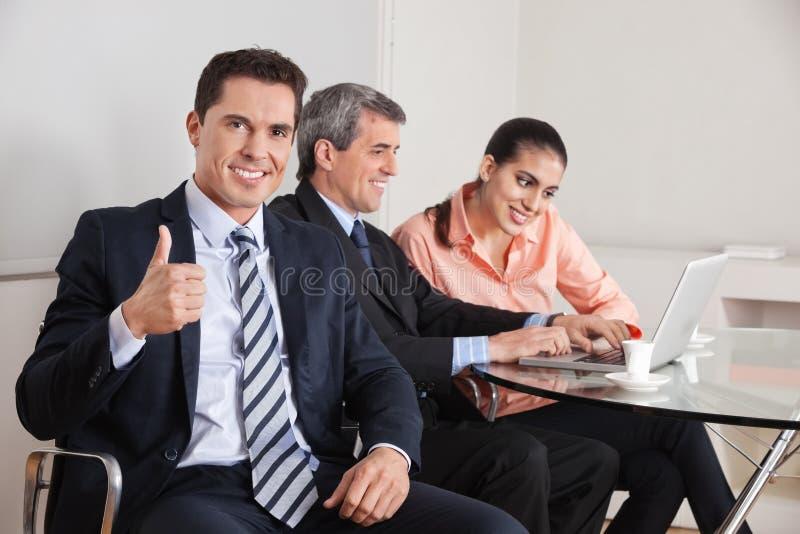 Director empresarial que prende seus polegares imagem de stock