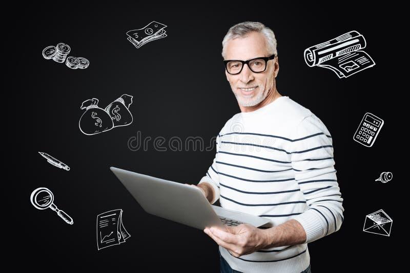 Director financiero positivo que se coloca con un ordenador portátil y que parece confiado fotos de archivo libres de regalías
