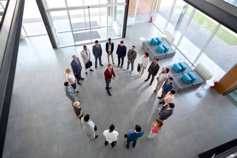 Director has meeting with employees. Young director has meeting with employees in circle in company hall stock photography