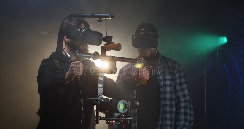 Director instructing a cameraman on a film set. Medium shot of a young director instructing the steadicam using cameraman on a film set royalty free stock image