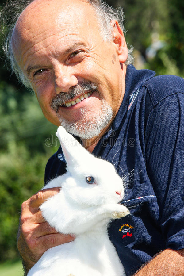 The director Luciano Capponi with a rabbit in her arms. Luciano Capponi is both author and director of film and theater and television, musician and composer royalty free stock image