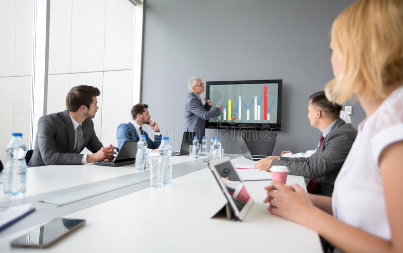 Director present company's business plan. Director of company present business plan while employees listen royalty free stock photo
