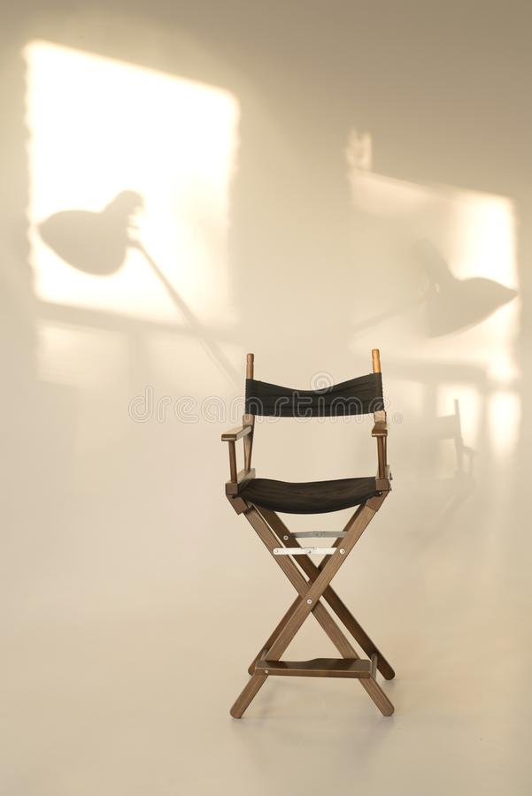 Director`s chair on a white background. shadows on the wall from the sun. light shades royalty free stock photos