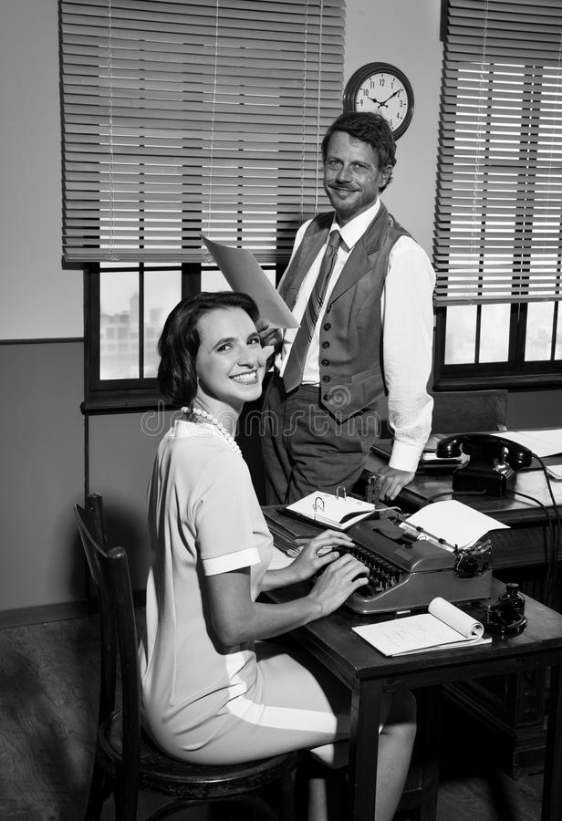 Director and secretary working together in the office. Director with paperwork and young secretary typing on typewriter in an elegant vintage office royalty free stock image
