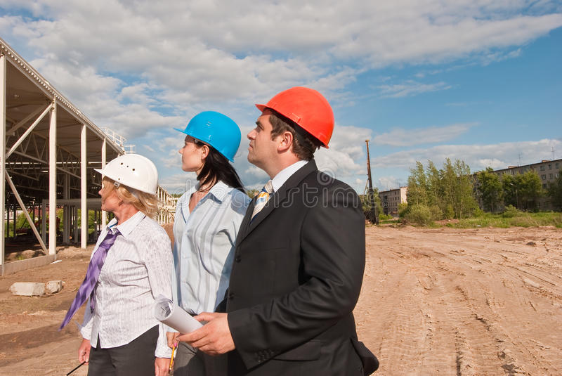 Director with subordinates on construction site. Director and engineers on construction site of shopping center royalty free stock photography