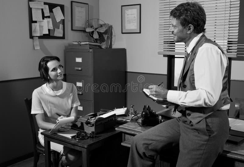 Director y secretaria del vintage que trabajan en la oficina foto de archivo