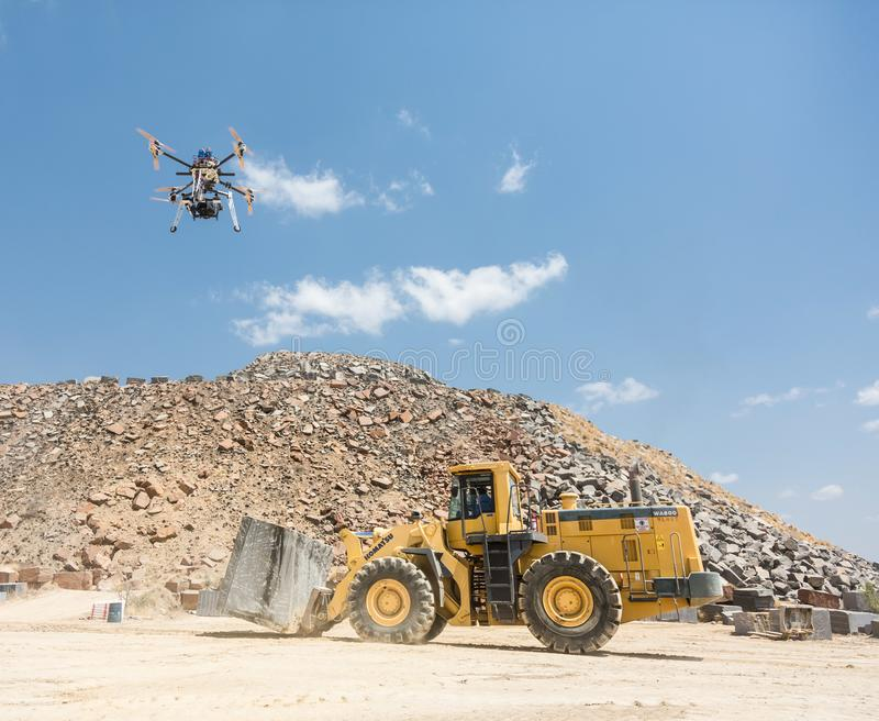 Film set and crew in Africa at open granite mine. Directors and crew on set for a video shoot on open granite mine using a drone to film mining machinery royalty free illustration