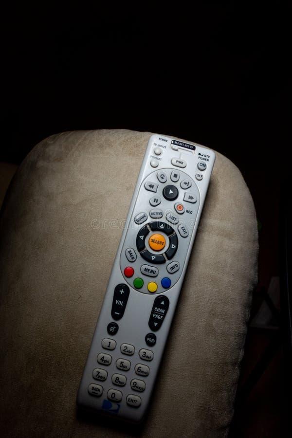 DirecTV remoto en el brazo del recliner con el un montón de copyspace fotografía de archivo