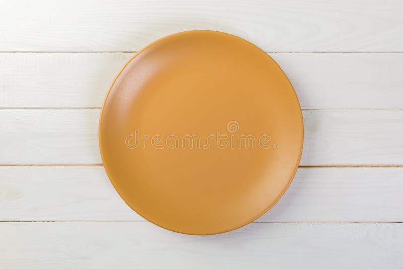 Directy boven Lege oranje steenschotel voor diner op witte houten achtergrond royalty-vrije stock fotografie